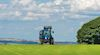 Blue tractor travelling along field