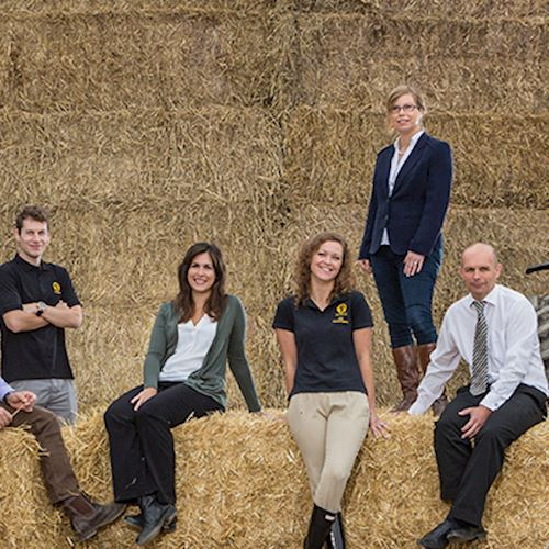 NFU Mutual Welshpool branch team assembled on hay bales next to green tractor