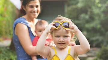 Girl wearing yellow swimsuit holding yellow sunglass on her head, mother in blue dress watching from behind