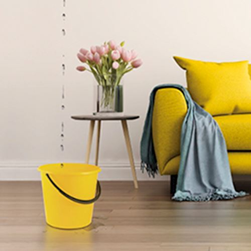ellow sofa with throw draped over arm, yellow bucket catching water leaking from ceiling