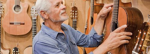 Grey haired and bearded man wearing blue flannel shirt looking at guitars hung on wall