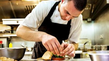 Young chef preparing sandwich in restaurant kitchen