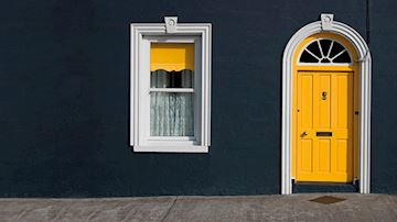 Black terraced house with yellow front door