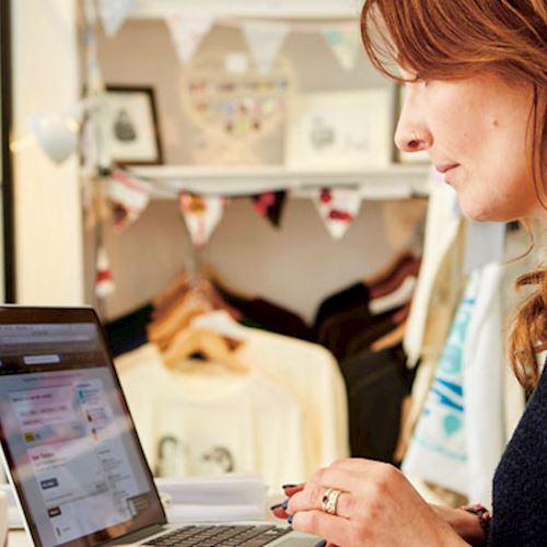 Clothes retailer working from laptop computer