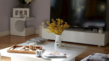 A suburban house living room, large screen TV, breakfast and flowers in a vase on the coffee table