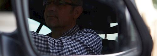 Male driver wearing gingham shirt in wing mirror of car