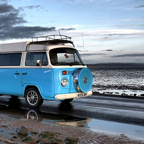 Blue and white Volkswagen campervan parked on costal road with tide out