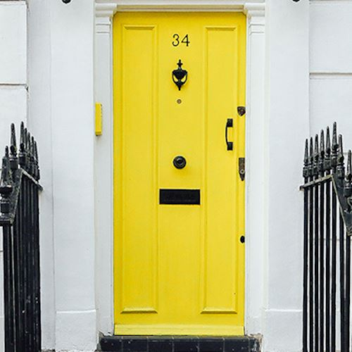 Yellow front door of white brick house with black railings on either side