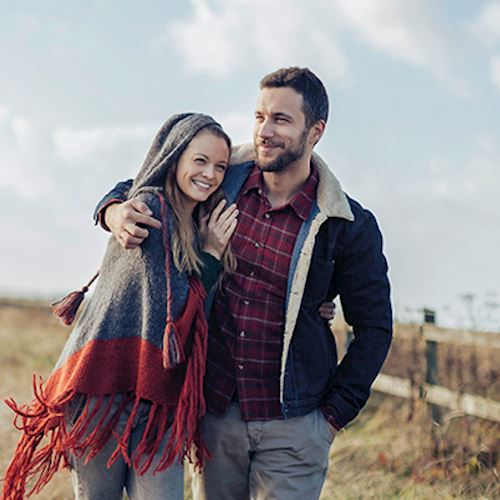 Young couple in autumnal clothing on country walk, man with arm around female partner