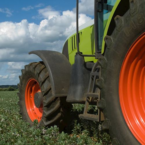 Green tractor with red wheels in crop field
