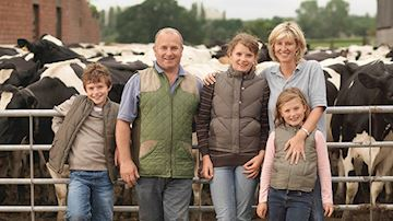 Cattle farming family, son, father, mother and two daughters in farming clothes