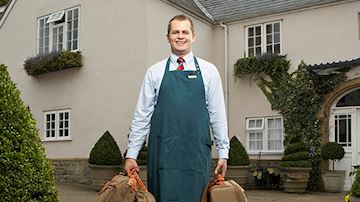 Hotel concierge holding bags wearing green apron