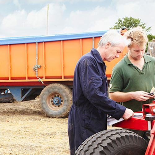 Two farmers, in blue overalls and green polo short, working next to equipment