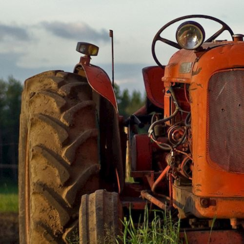 Red vintage tractor with exposed wires in empty field