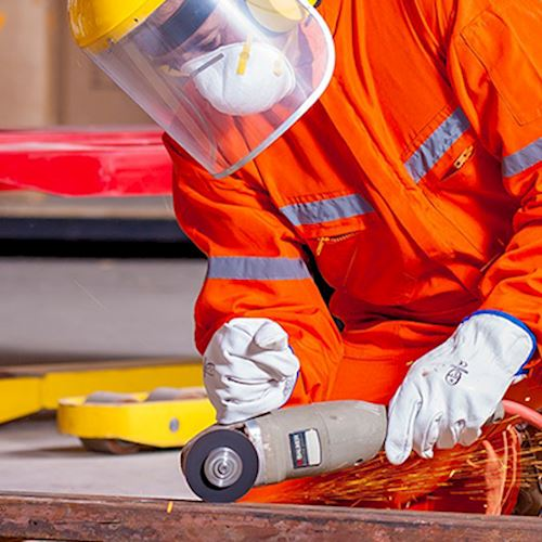 Worker wearing personal protection equipment and high visibility jacket using angle grinder