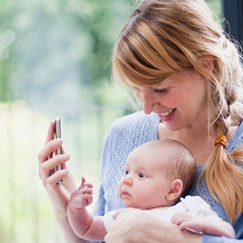Auburn haired mother in blue cardigan showing young baby in white baby grow smartphone