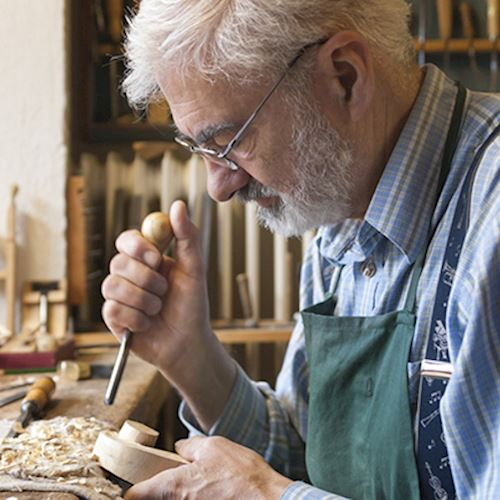 Grey haired and bearded man in green apron carving violin