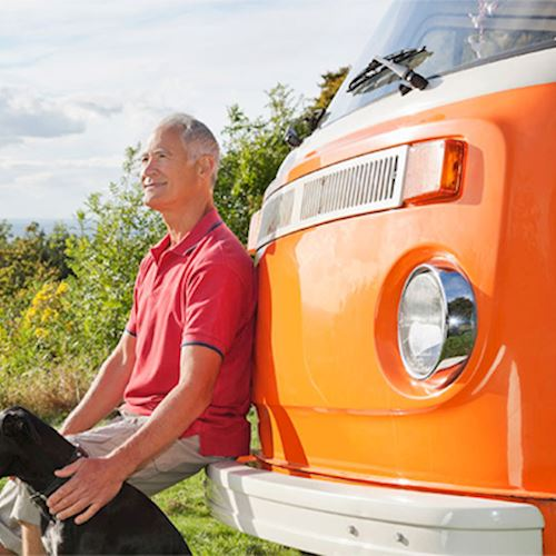 Grey haired man wearing red polo shirt a top hill with black dog resting against orange Volkswagen campervan