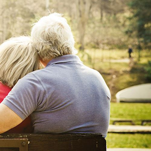 Grey haired couple sat on park bench with back to shot, man wearing blue polo shirt has arm around lady in red caridgan