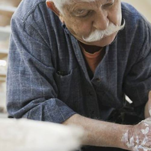 Grey haired man with moustache throwing and shaping clay pot