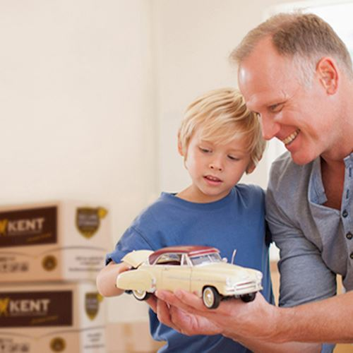 Father showing son toy car during house move
