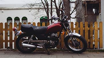 Red motorcycle, leather seat, stood next to wooden fence