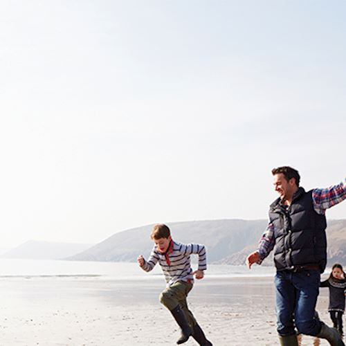 Family of grandparents, son and grandson and granddaughter running across beach with tide out flying multicoloured kite