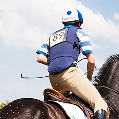 Three day eventer wearing blue spotted riding hat, blue and white polo shirt and blue body protector competing on black horse
