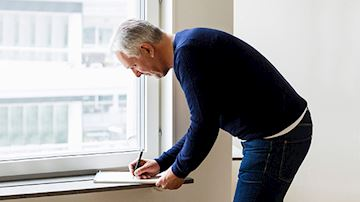 Grey haired property own in jumper and jeans signing contracts next to window