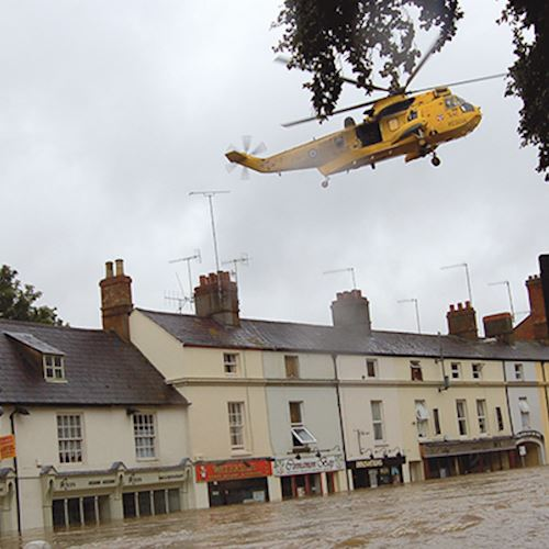 Helicopter flies above a flooded street as a man looks on
