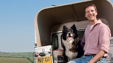 Farmer and sheep dog sit on edge of land rover