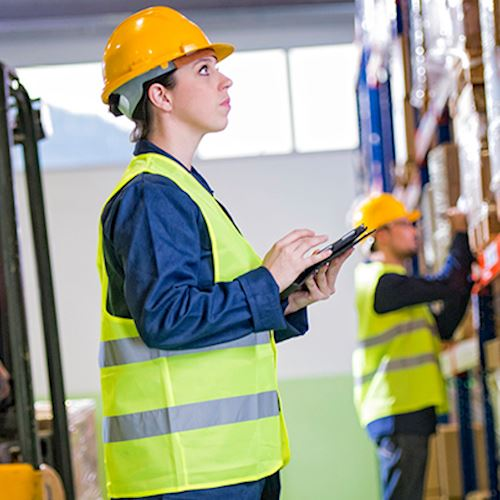 Woman in hard hat and fluorescent vest taking stock in a warehouse