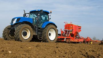 Tractor driving across field sewing seeds