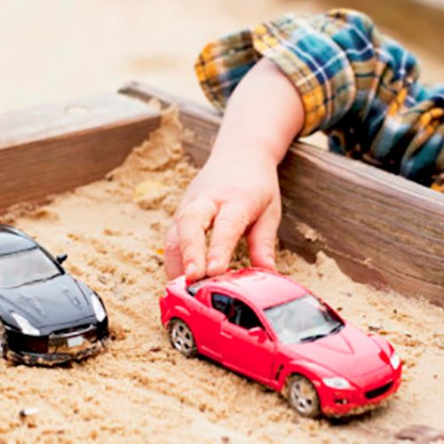 Child playing with toy cars on table