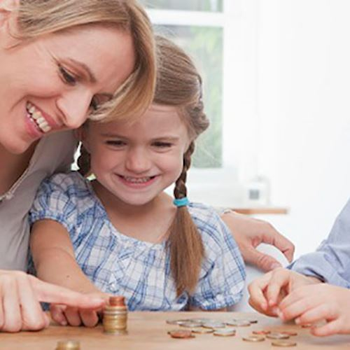 Woman teaching her two daughters abour money