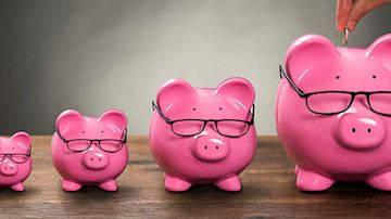 Four piggy banks wearing glasses