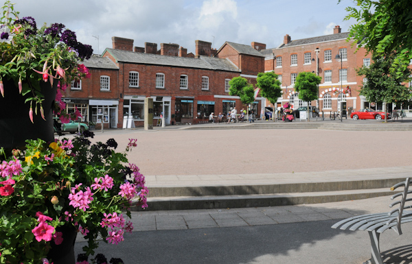 Crediton Square viewed from between flowers and a bench