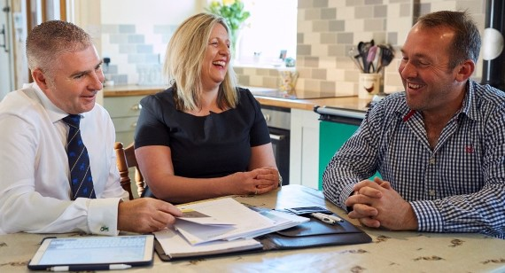 Financial adviser in kitchen with customer laughing