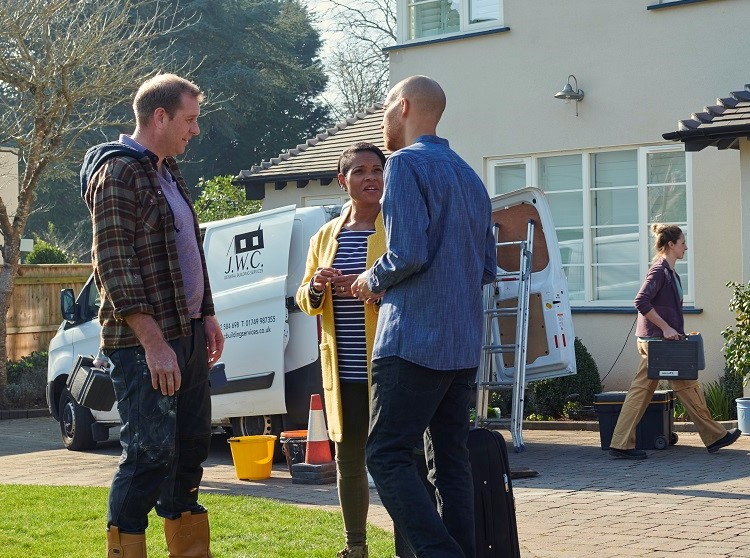 Tradesman and couple outside home