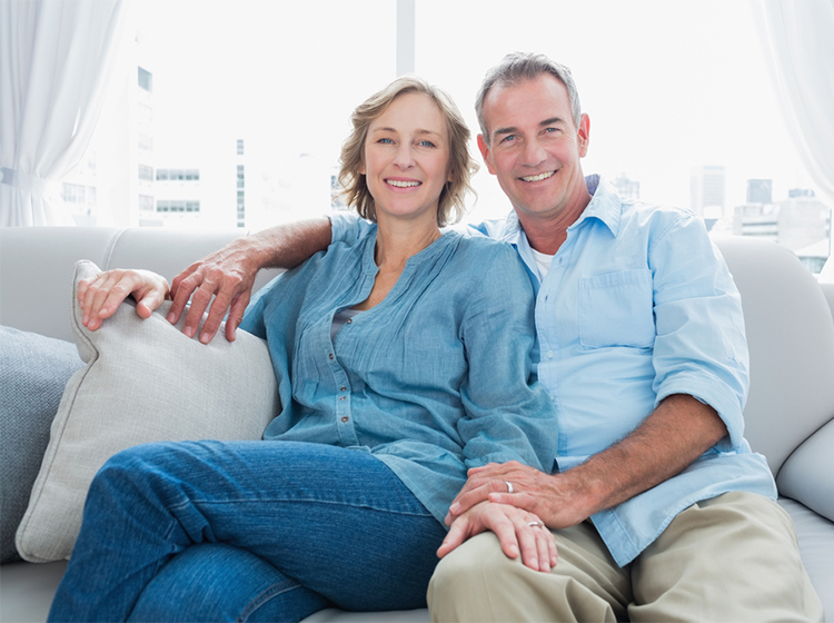 Blonde haired lady and grey haired male in blue shirts sat on white sofa in front of window