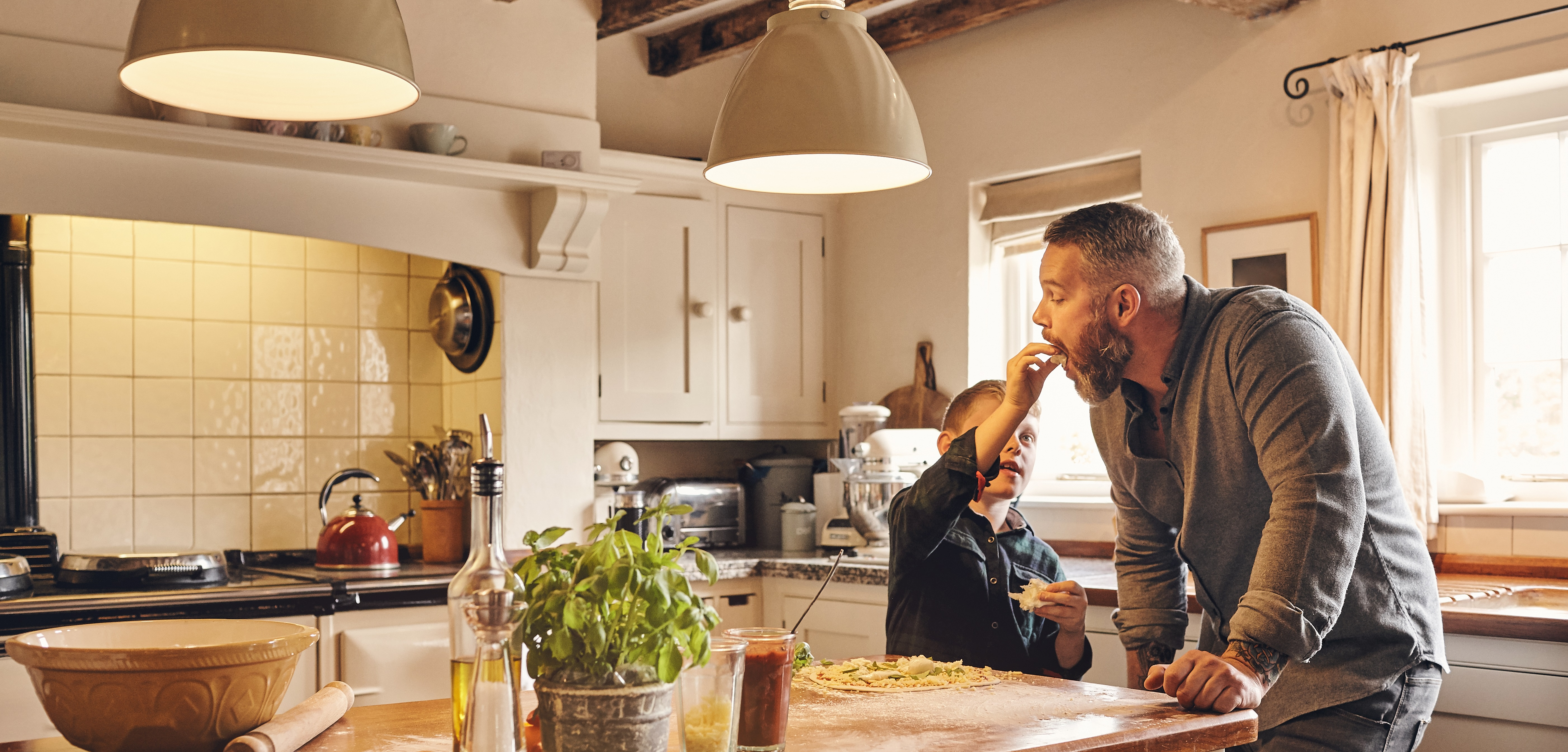 Son playfully feeding dad in kitchen